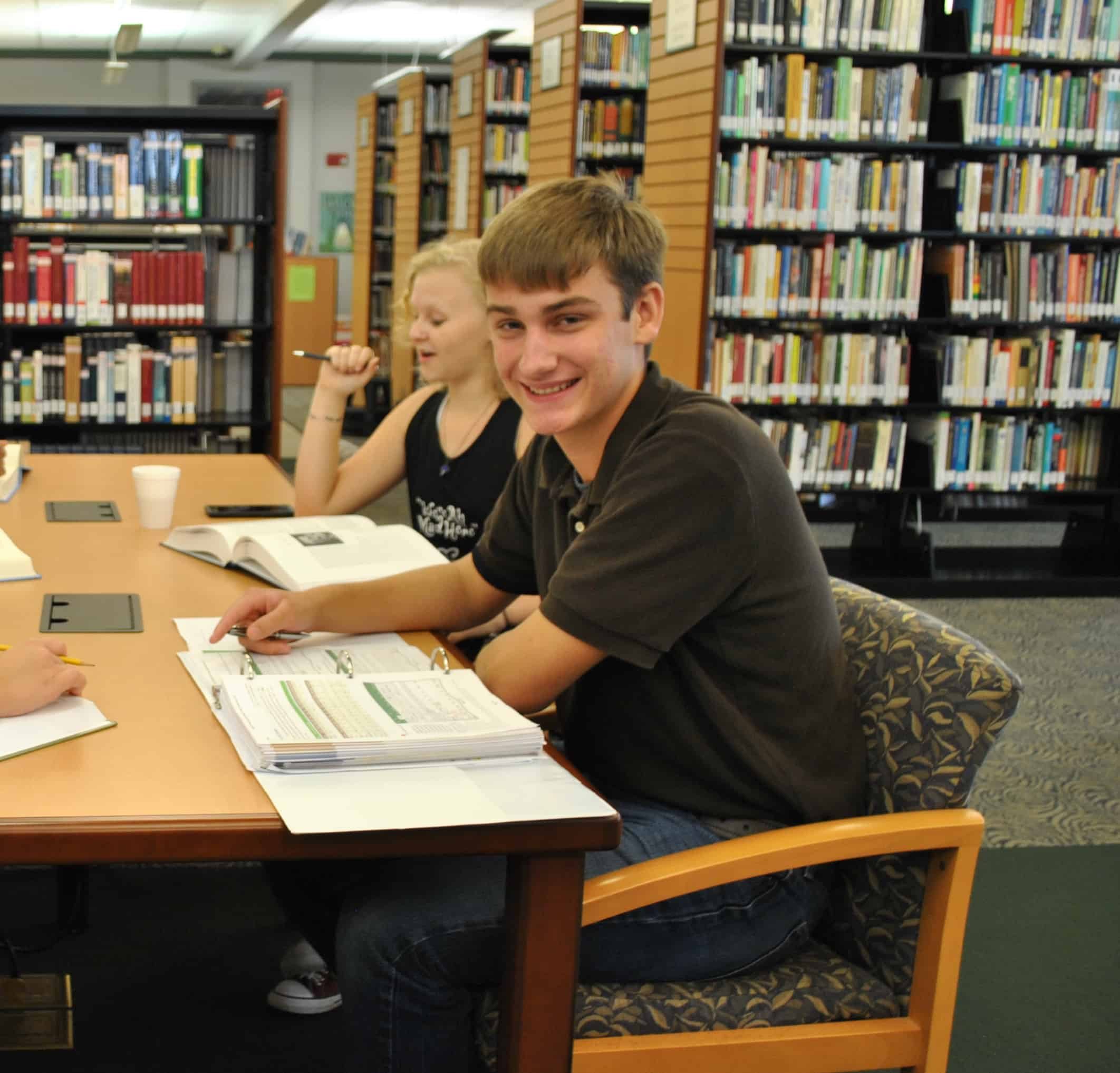 Noah Brack, sitting at table in library smiling.