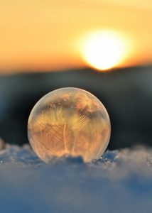 frost-etched orb on frozen blue surface in winter sunlight