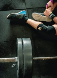 Person sitting on a gym floor beside a barbell with weight plates on it.