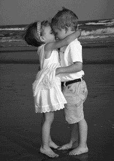 Junge und Mädchen küssen sich am Strand