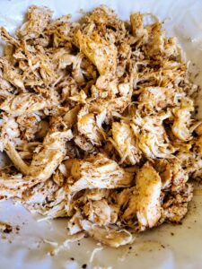 Mix spices with shredded chicken