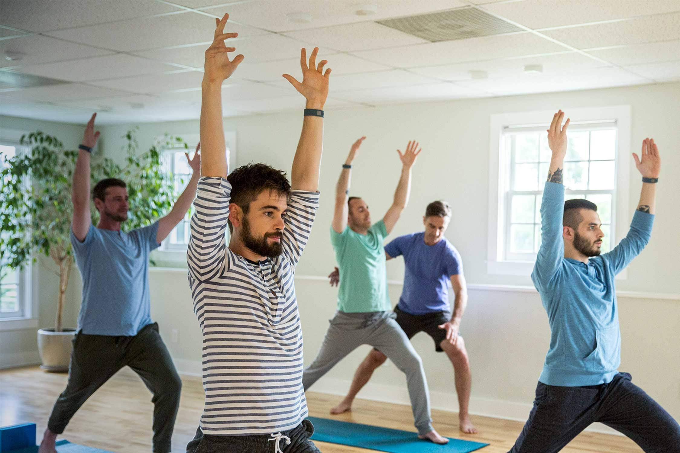 A group of men take a yoga class in bright room at Mountainside