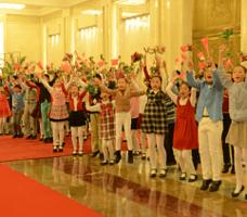 Puluhan anak-anak memegang bendera RI dan RRT berlompatan ikut menyambut kedatangan Presiden Jokowi, di Balai Agung Rakyat, Beijing, Kamis (26/3)