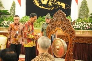 Presiden Jokowi memukul gong tanda pembukaan Munas Gabungan Pengusaha Jamu Tradisional ke-7, di Istana Negara, Jakarta, Senin (25/5)