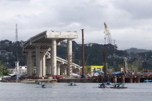 Sejumlah perahu mengangkut penumpang, melintas dekat proyek pembangunan Jembatan Merah Putih (JMP), di pantai Desa Galala, Sirimau, Ambon,