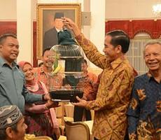Presiden Jokowi mengangkat burung kenari hadiah yang diberikan pedagang tradisional yang telah diundangnya makan siang, di Istana Negara, Jakarta, Kamis (3/9) siang