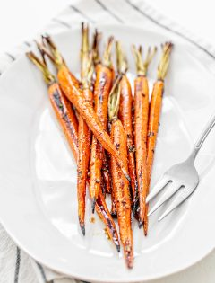 whole roasted carrots on a white plate