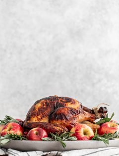 turkey on a platter with apples and sage