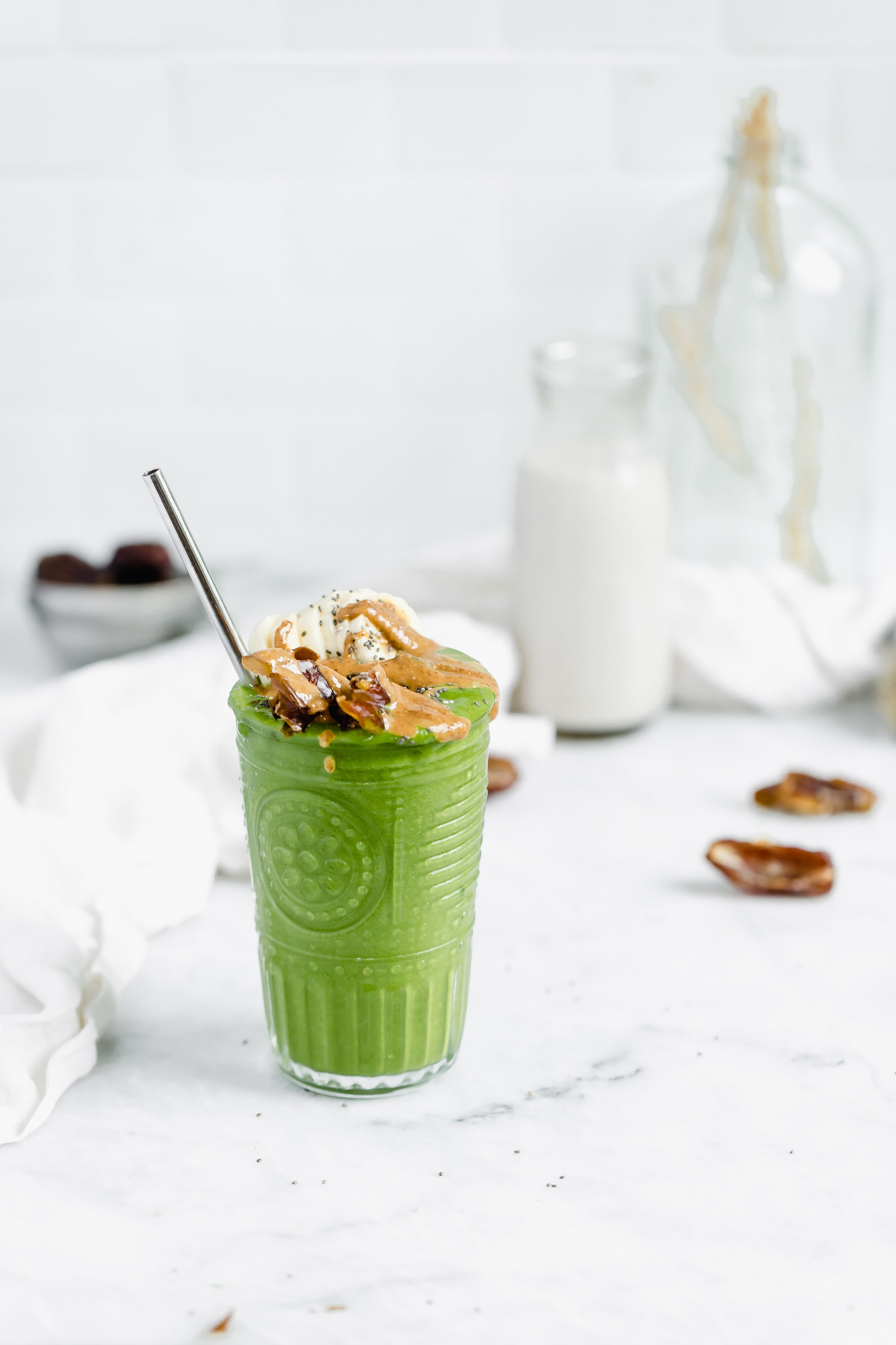 green smoothie topped with bananas, dates, almond butter, and chia seeds