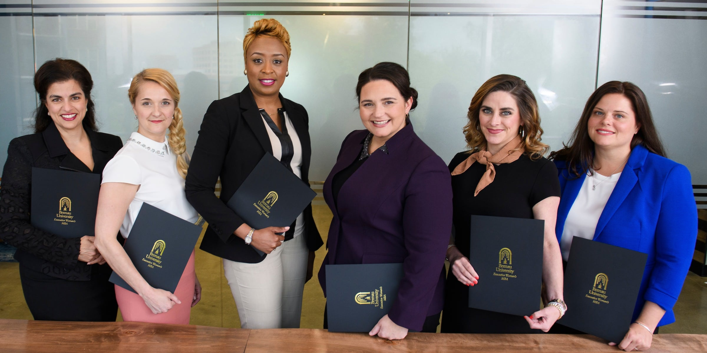 Row of professional, women executives holding folders with Brenau logo