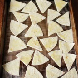 tortilla wedges placed on a baking pan ready to go into the oven