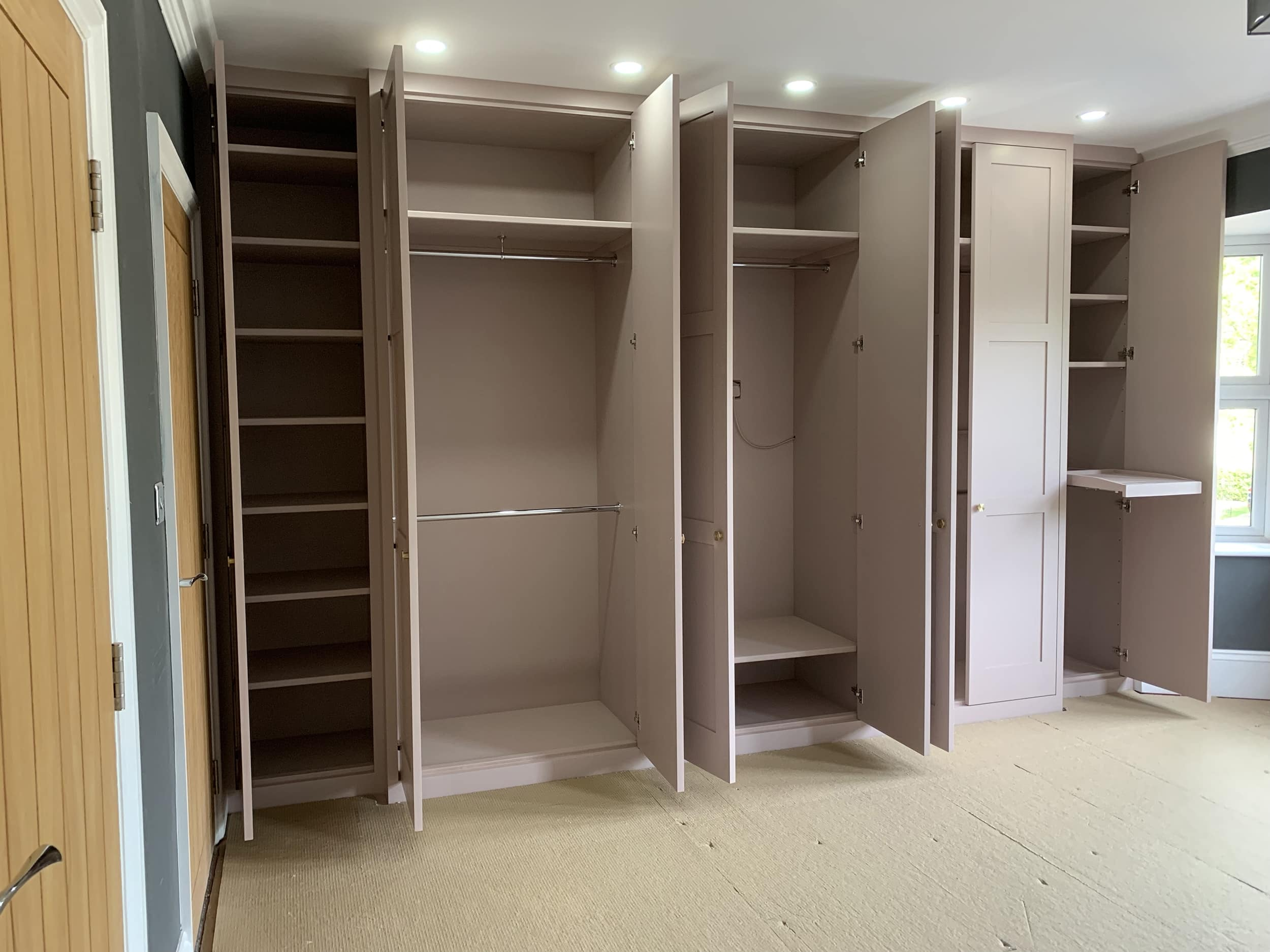 Wardrobe interior with shelves and hanging space.