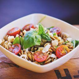 insalata di pasta con basilico, pomodorini, fusilli e mozzarella di bufala a tocchetti in una ciotola bianca