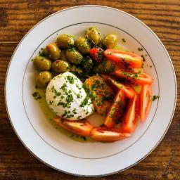 burrata di bufala con pomodori e olive in un piatto su tavolo di legno