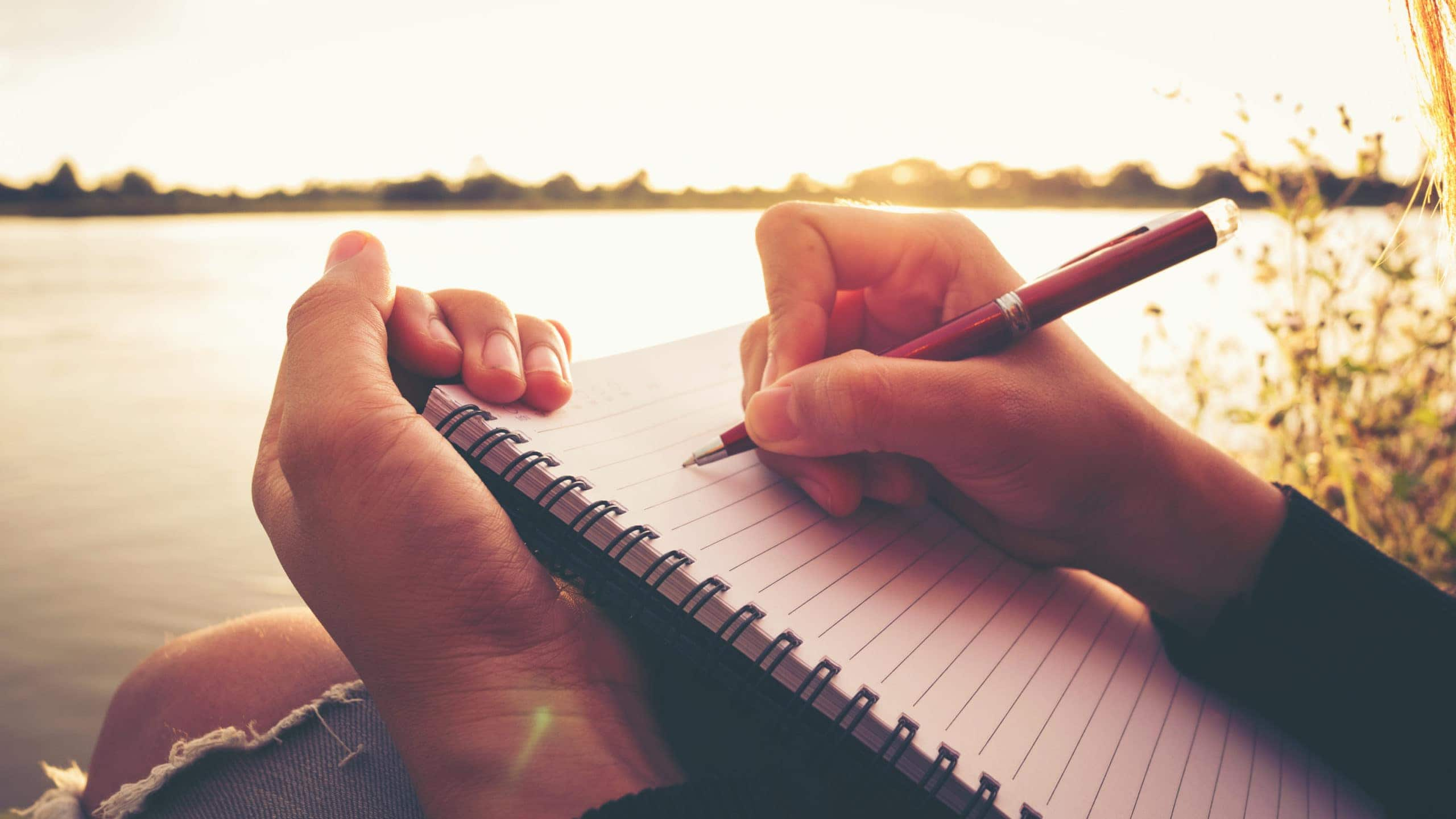 Person writing in journal near lake