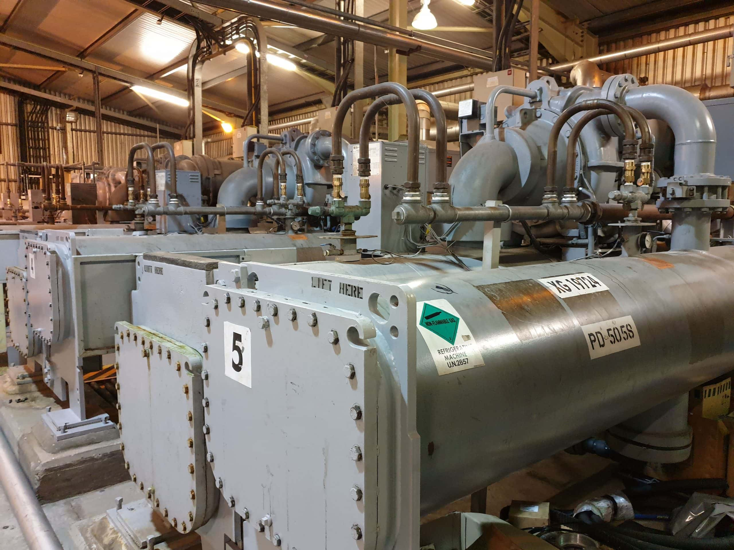Plant room with row of 5 grey centrifugal chillers for service, maintenance and repair