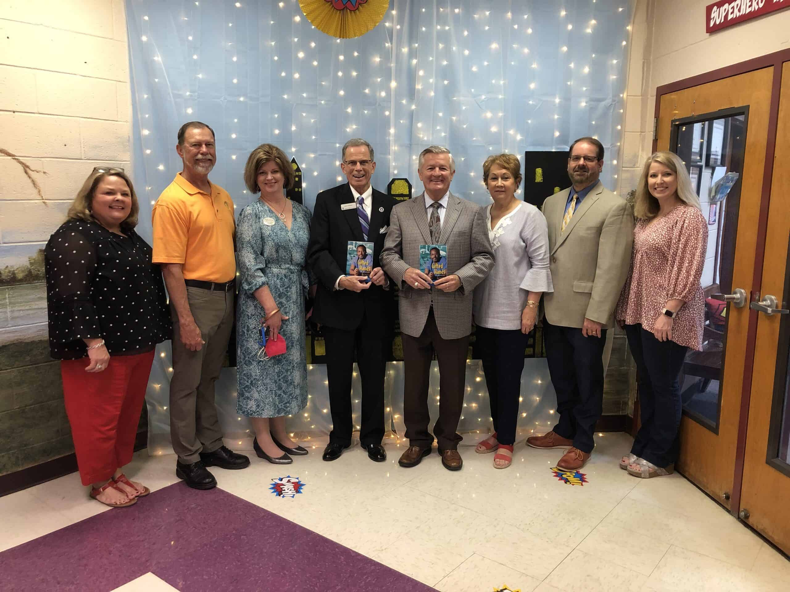 Members of OFTC, the Dublin and Cochran Rotary Clubs, Bleckley County Superintendent, and Bleckley County Elementary School Principal and Assistant Principal gathered for a photo prior to handing out the book Gifted Hands to 180 fifth grade students at Bleckley County Elementary School.