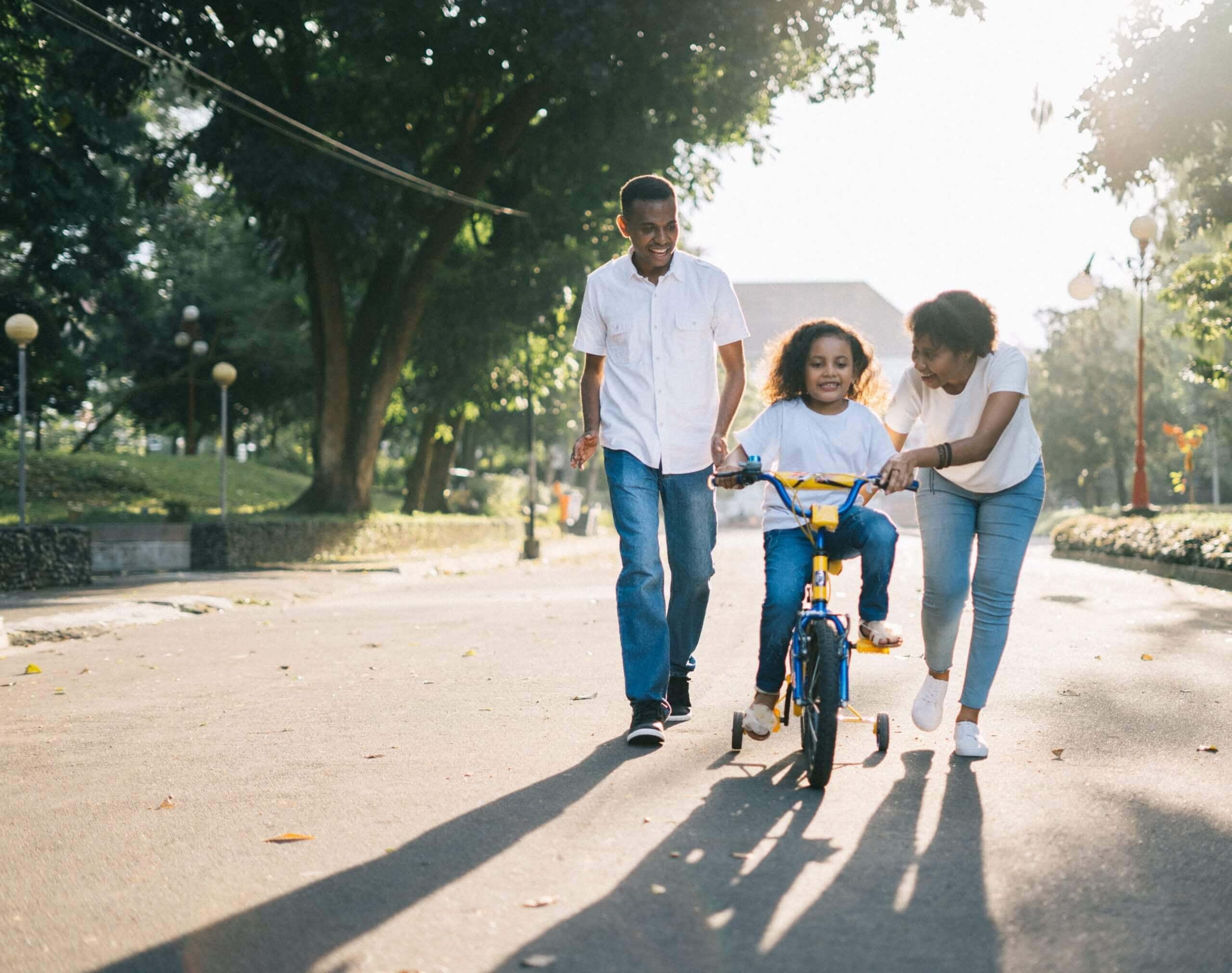 Parents teaching their child how to ride a bike- Pexels stock image