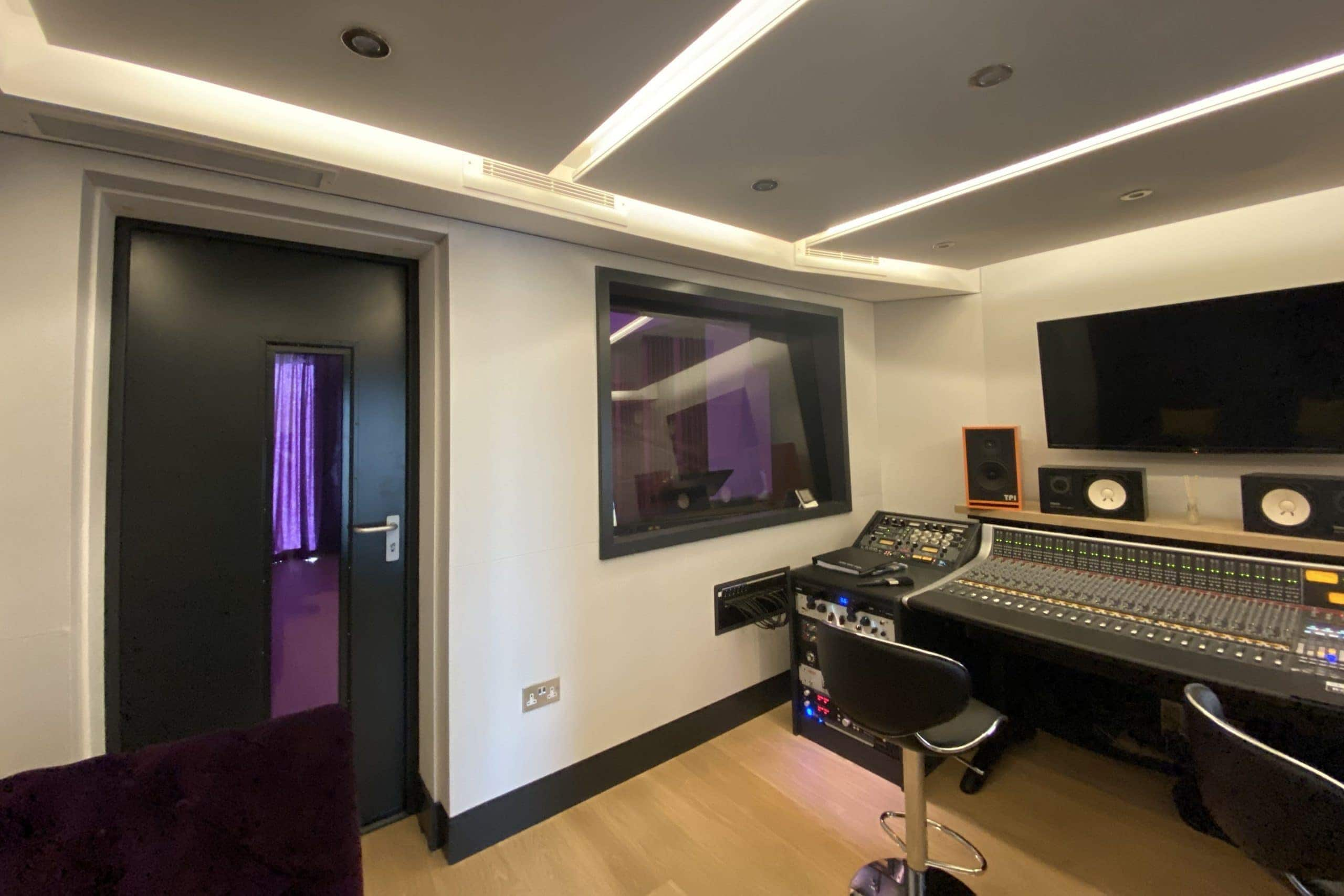 View of multiple white vents of ducted air conditioning system in Arden barn conversion in Lingfield in a music studio over control desk fitted by SubCoolFM