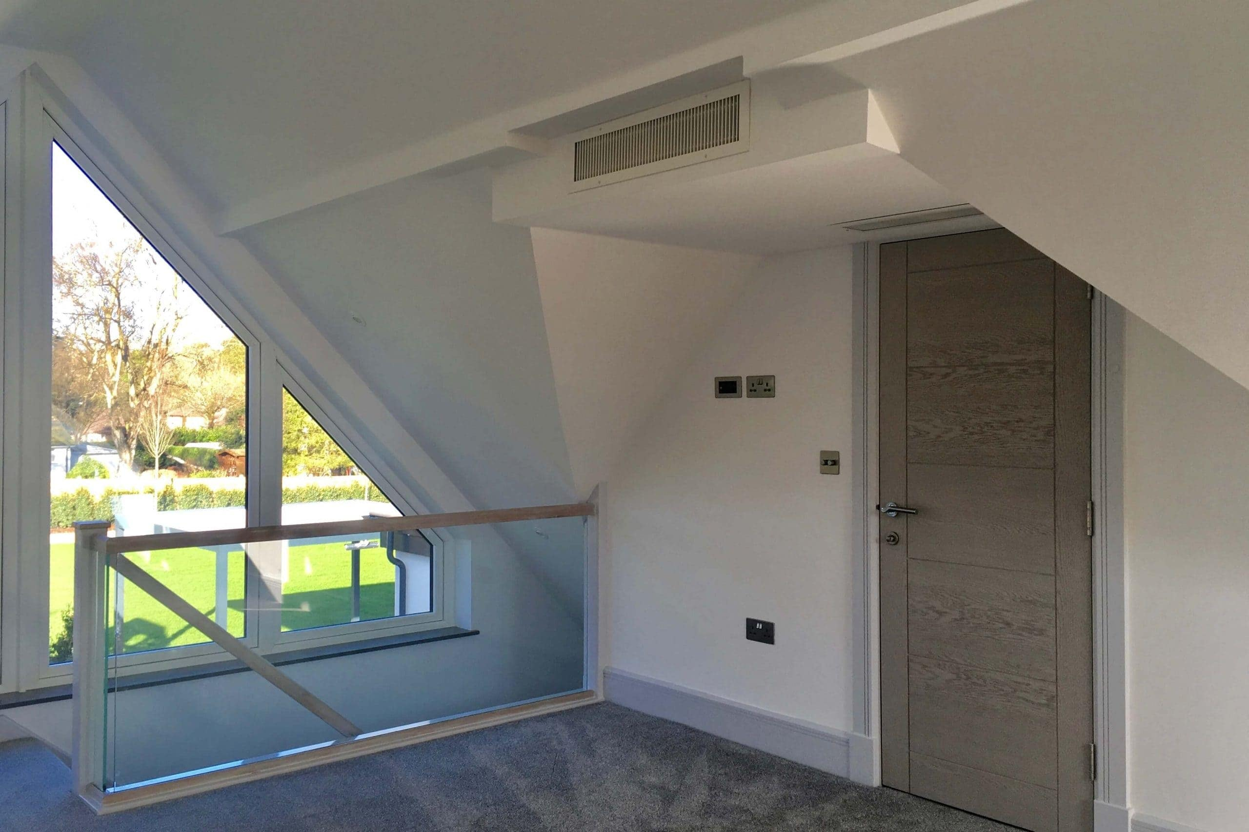 Scandia Hus new build project upstairs bedroom side view with 2 air grills by door as part of MVHR and air conditioning system by SubCool FM