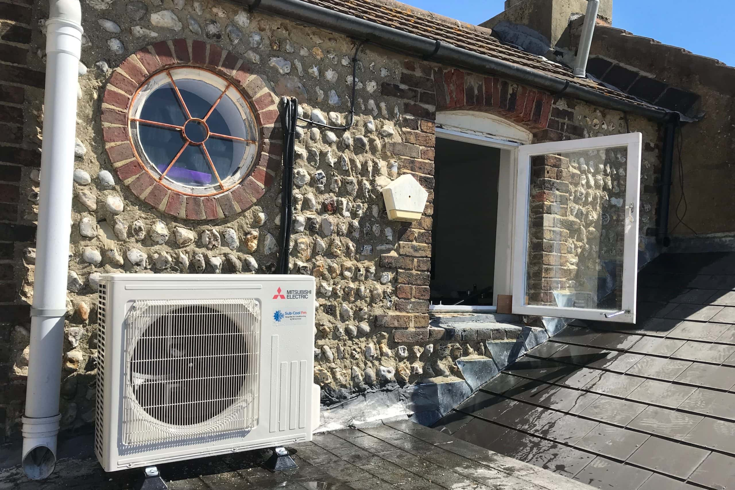Domestic external Mitsubishi Electric air conditioning unit on upper floor roof