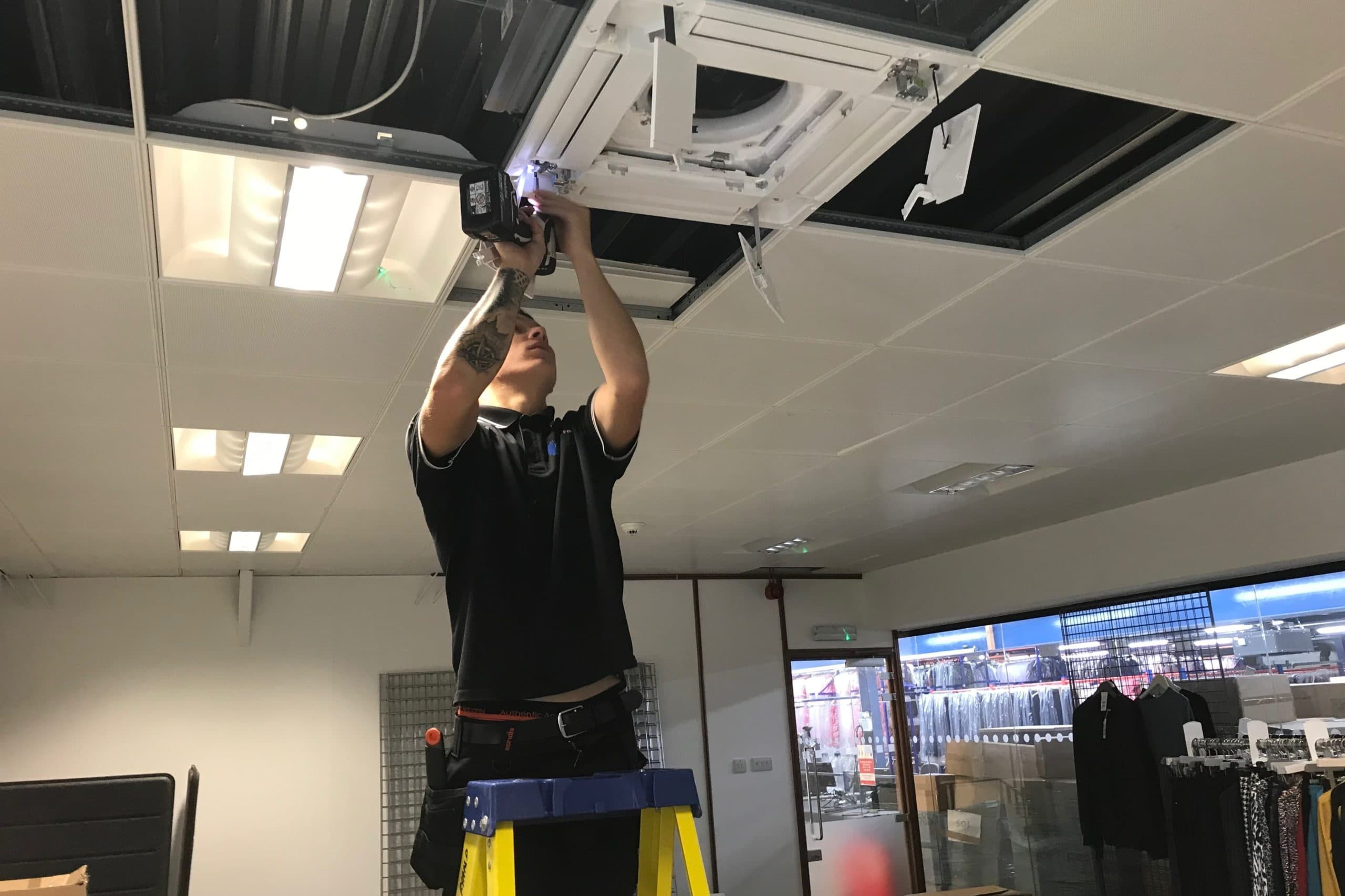 SubCool Fm air conditioning engineer drilling ceiling at clothing retailers