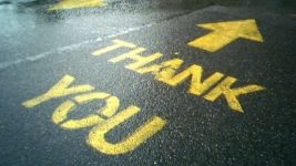 Image: The words Thank You painted on a wet street with an arrow