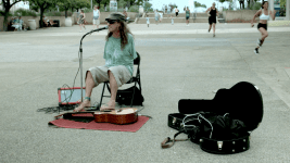 Image: Mark Goffeney playing guitar in a park with his feet