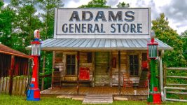 "Image: A small building with a large sign reading ""Adam's General Store"""
