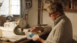 Image: man painting ink on a piece of paper