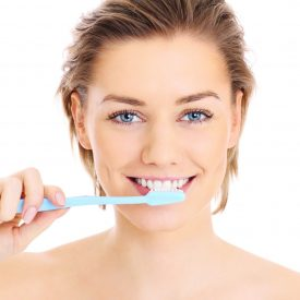 woman brushing her teeth lightly