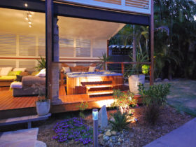a stylish white custom aluminum shutter for extra privacy for the hot tub on a roofed deck