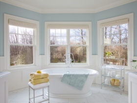a traditional bathroom with soft blue walls and white tile porcelains to give a relaxing sensation