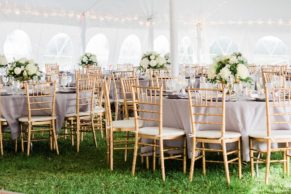 Outdoor wedding reception with gray linens and gold chiavari chairs, featuring white and green floral centerpieces by Kittelberger Florist NY.