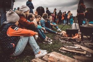 A group of children sitting next to a campfire