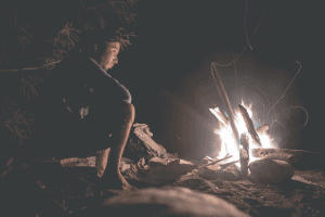 man looking mesmerized by campfire during the night