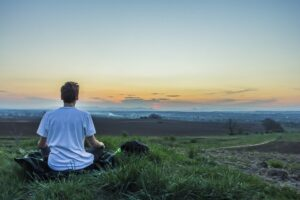 Meditating in field - yoga for wellbeing