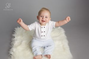 Baby boy sitting up and smiling on grey background