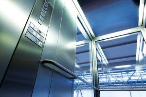 Innenraum eines Glasaufzugs mit Metallleiste.
