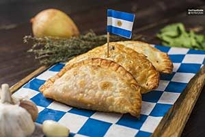 Three empanadas with a little Argentine flag sticking out of the middle