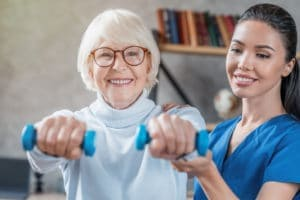 Senior woman training with physical therapist at home