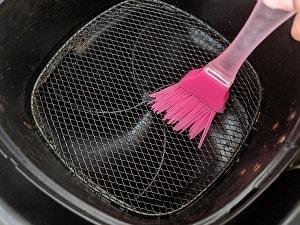 preparing the air fryer basket by brushing oil.