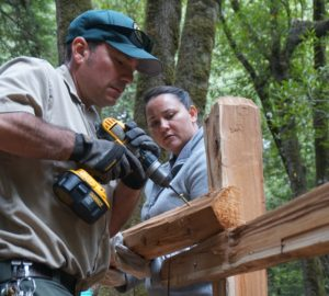 A volunteer holds up a fence beam for the park ranger to secure.