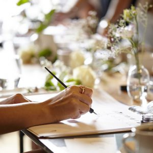 A PERSON HANDWRITING AND LEARNING CALLIGRAPHY AT A LONDON CALLIGRAPHY COURSE IN A BEAUTIFUL SETTING