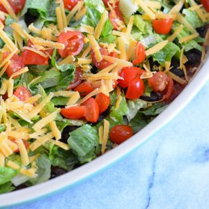 Taco dip topped with cheese, lettuce and tomatoes.
