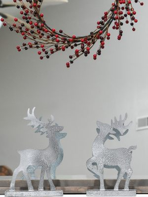 Christmas reindeer figurines made from paper and painted to look like metal on a Christmas mantel.