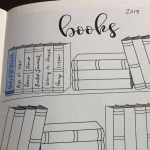 A reading journal example with a bookshelf printable in a bullet journal