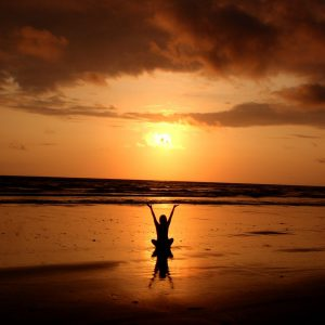 Reiki practitioner welcoming sunrise over ocean with outstretched arms