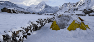 A tent under a lot of snow in the mountains