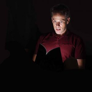 Bright light shining from inside a book onto the face of a man in the dark